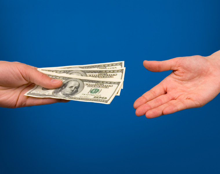 One hand gives money in other hand over blue background